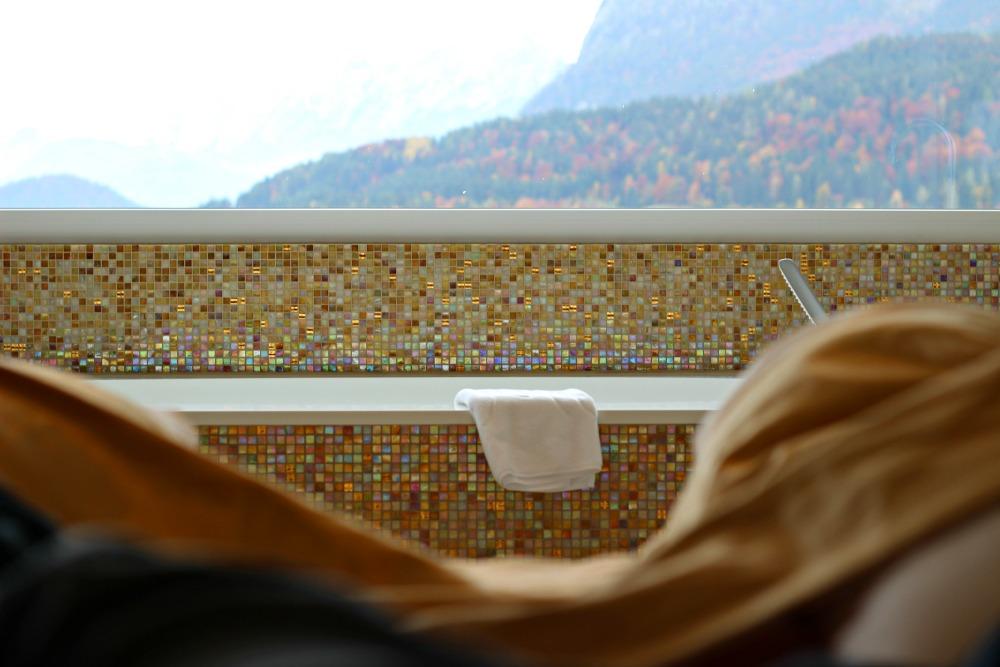 Ausblick vom Bett auf die freistehende Badewanne in der Suite Skyfall im Juffing und auf die Berge von Thiersee