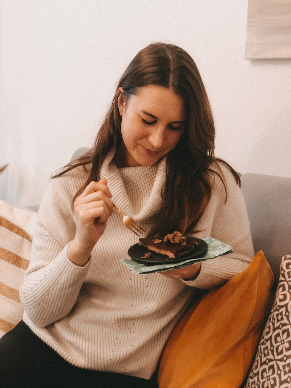 Frau-sitzt-auf-dem-Sofa-und-isst-ein-Stück-Kuchen